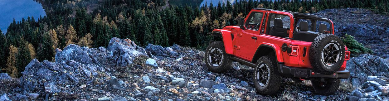 Jeep Wrangler parked on a rocky mountain in front of trees
