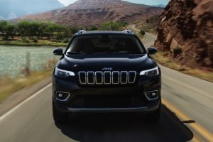 Front of 2020 Jeep Cherokee driving forward on an winding country road by water