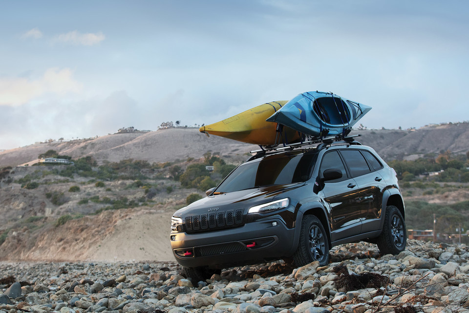 2020 Jeep Cherokee parked on a rocky beach with kayaks on top