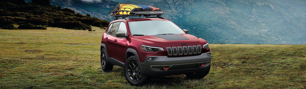 2020 Jeep Cherokee parked on a grassy mountaintop with gear on the top