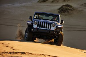 Front of 2020 Jeep Wrangler driving on sand in a desert