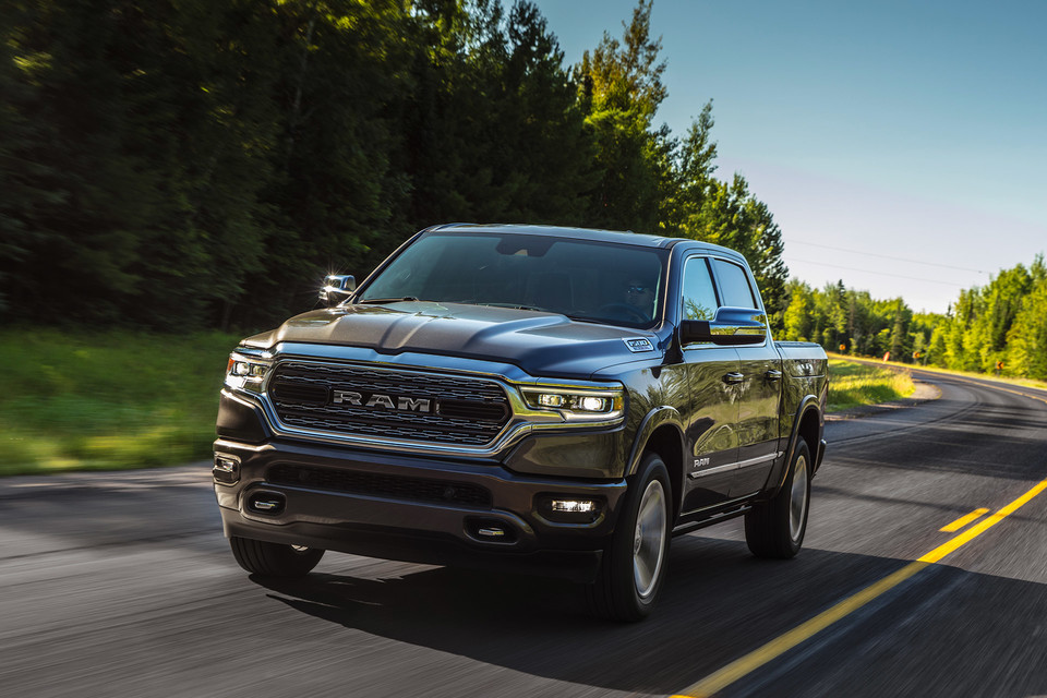 2020 Ram 1500 in grey driving on a highway in between a forest