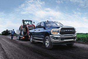 Ram 2500 towing a tractor with a man walking beside it