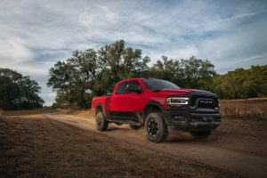Red Ram 2500 covered in mud driving down a dirt road