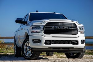 2020 Ram 2500 in white with a close front view, parked in front of water