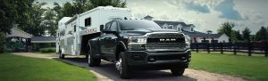 2020 Ram 3500 parked with fifth-wheel in front of a big house