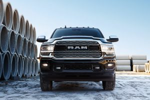 Front of 2020 Ram 3500 next to large stack of pipe