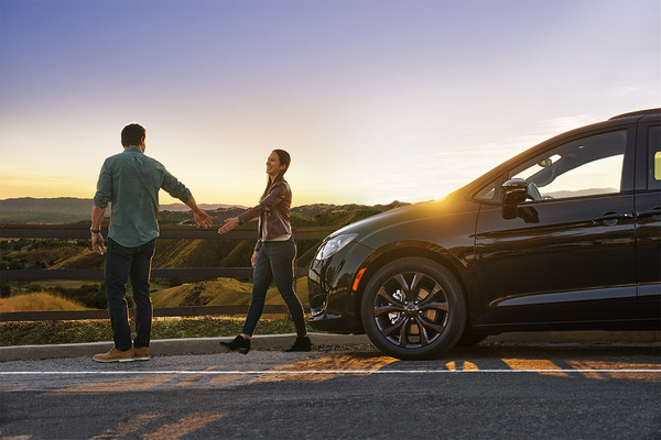 Couple about to hold hands in front of Chrysler Pacifica