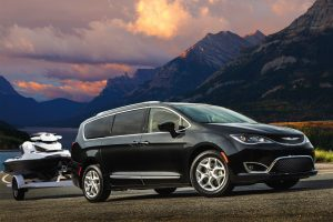 2020 Chrysler Pacifica towing a seadoo in front of mountains and a lake