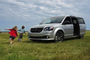 Dodge Grand Caravan in grey parked in field with kids playing around it