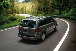 Rear view of Dodge Grand Caravan driving along a winding country road
