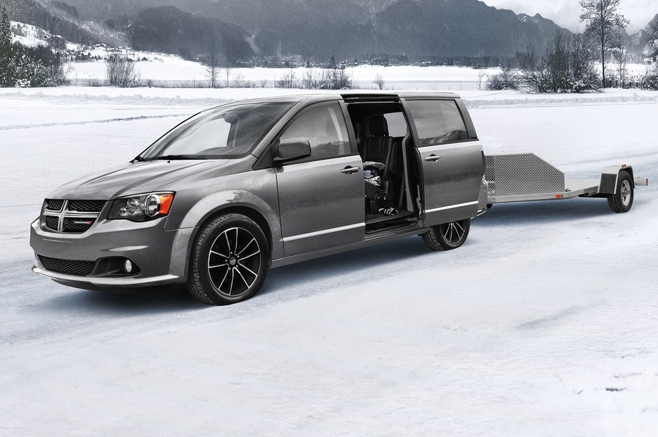 Dodge Grand Caravan parked in a snowy field with a trailer