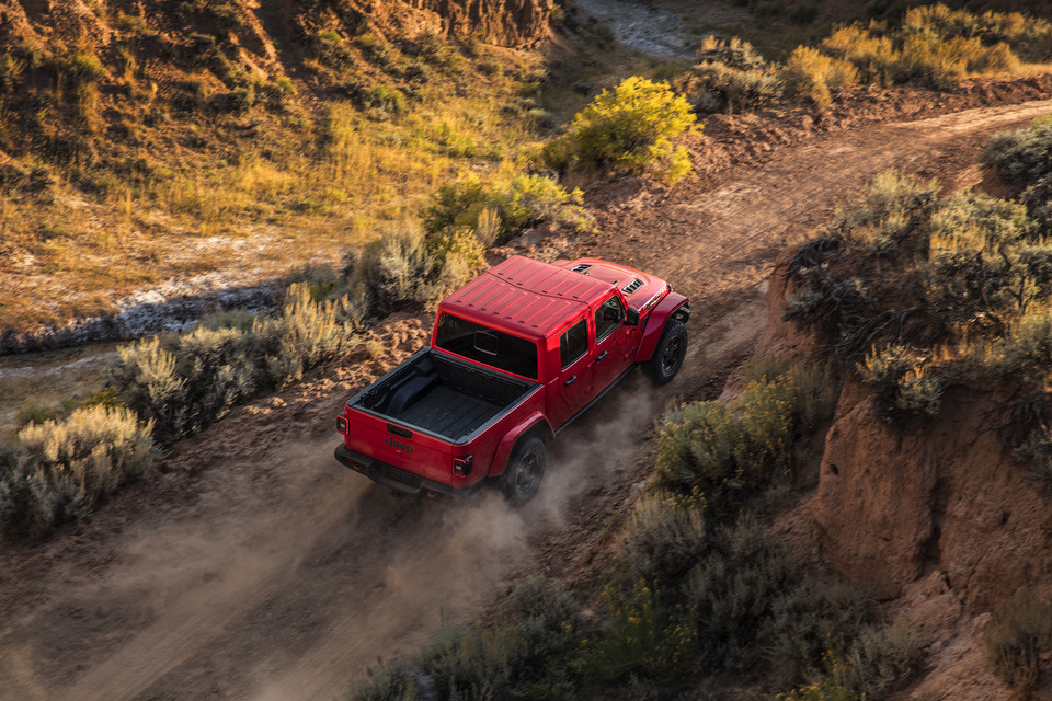 Overhead of red Jeep Gladiator driving uphill on a dusty road