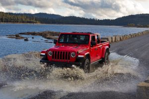 2020 Jeep Gladiator driving through a big puddle on a road next to a lake