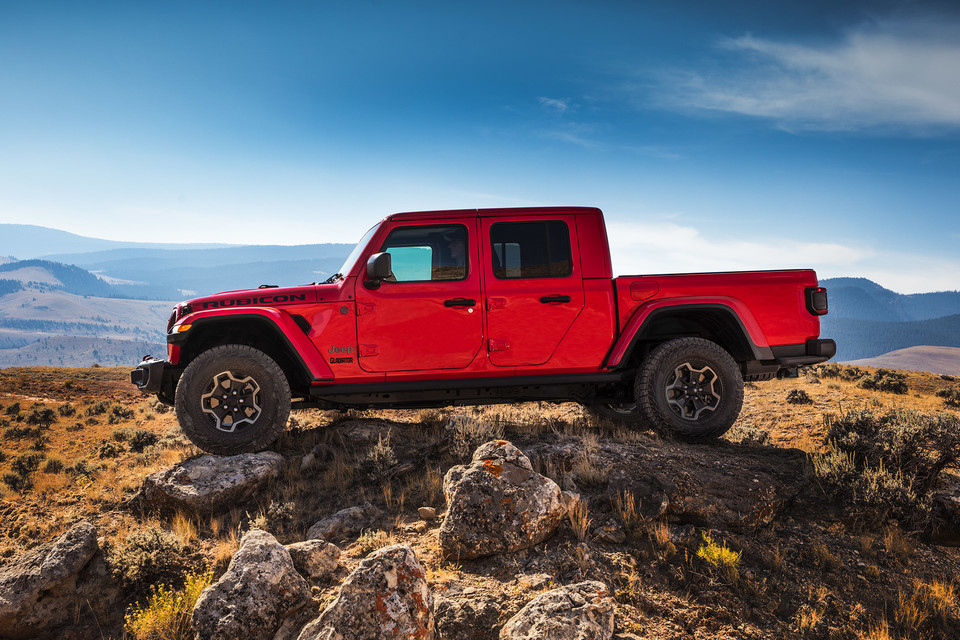 Side exterior view of red Jeep Gladiator parked on a rocky hill