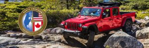 2002 Jeep Gladiator driving on rocks with a Truck of the Year graphic badge