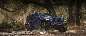 2020 Jeep Wrangler in blue driving through some water in front of large trees