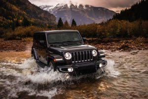2020 Jeep Wrangler in black driving through a creek