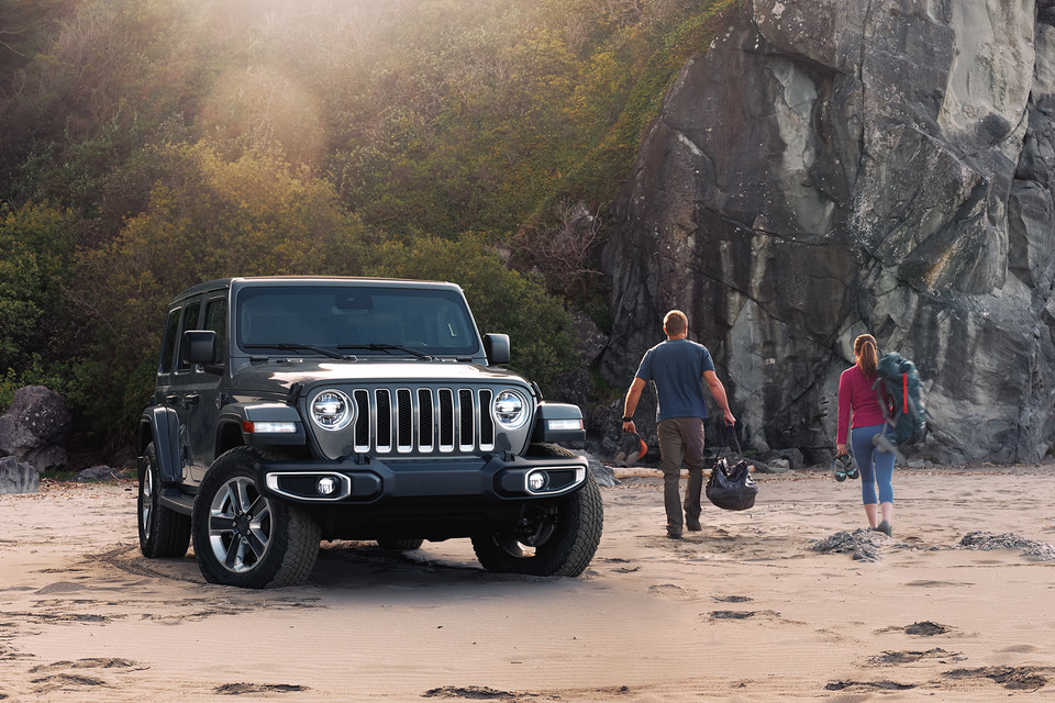 Two peopled walking away from a parked Jeep Wrangler on the sand