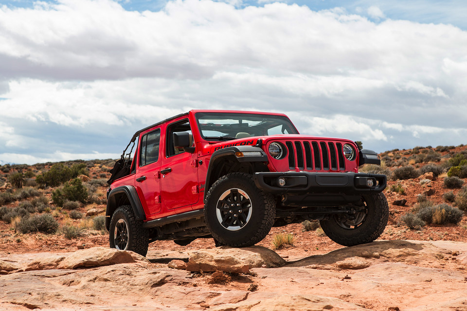2020 red Jeep Wrangler parked by desert bushes