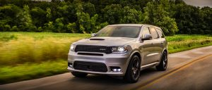 Side front profile of Dodge Durango driving next to forest