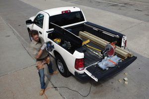 Cargo and construction gear in the back of a Ram 1500 Classic with man getting gear from it